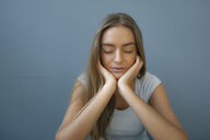 Portrait of young woman with eyes closed and head in hands relaxing - KNSF05013