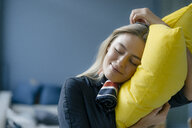 Portrait of smiling young stewardess with yellow pillow - KNSF05037