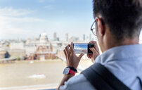 UK, London, man taking a picture of the city from roof terrace - MGOF03803