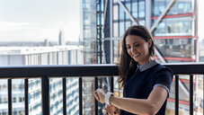 UK, London, smiling woman using smartwatch on a roof terrace - MGOF03809