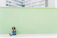 Man sitting infront of green wall - INGF02823