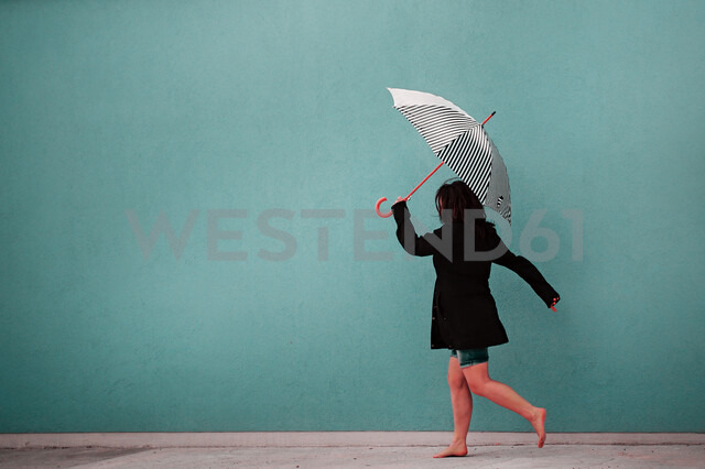 Woman with umbrella walking bare feet with copy space - INGF02967 - Ingram Image/Westend61