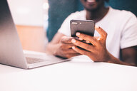 Close-up of man using smartphone and laptop - INGF02985