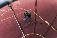 Young man playing basketball on basketball ground - UUF15553