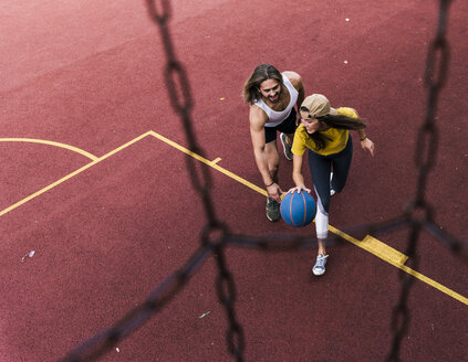 Young man and woman playing basketball on basketball ground - UUF15556