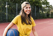 Happy young woman playing basketball - UUF15559