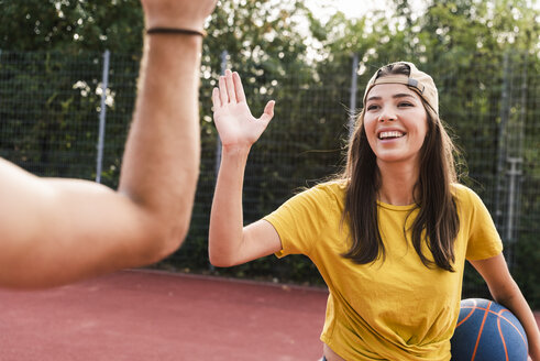 Young man and young woman high-fiving after basketball game - UUF15562