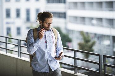 Young businessman walking in parking garage, using smartphone - UUF15616