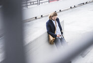 Young businessman with skateboard, leaning on wall, using smartphone - UUF15622