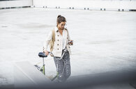Young businesswoman with backpack, pushing bicycle, using smartphone - UUF15625