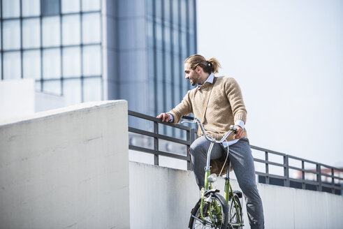 Young man sitting on bicycle, waiting at a railing - UUF15628