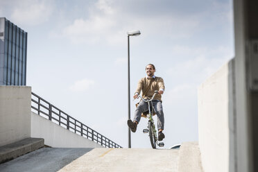 Laughing businessman riding down a ramp on his bicycle - UUF15631