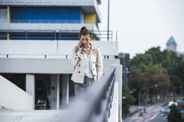Young businesswoman using smartphone in he city - UUF15634