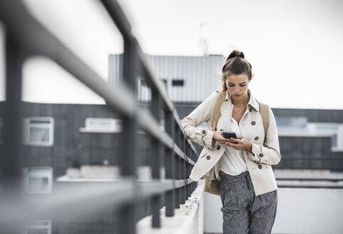 Young businesswoman using smartphone in he city - UUF15637