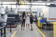 Three women with tablet talking in factory shop floor - DIGF05281