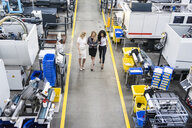 Three women with tablet walking and talking in factory shop floor - DIGF05290