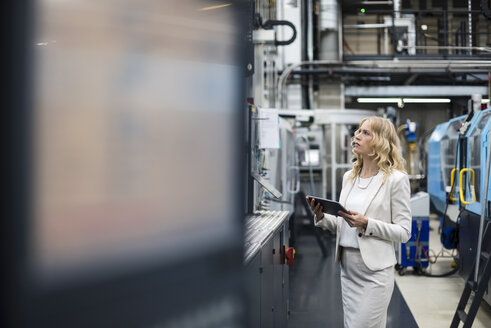 Woman with tablet at machine in factory shop floor looking around - DIGF05293