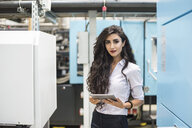 Portrait of confident woman holding tablet in factory shop floor - DIGF05305