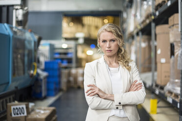 Portrait of confident woman in factory storehouse - DIGF05323