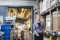 Portrait of confident woman with tablet in factory storehouse - DIGF05332