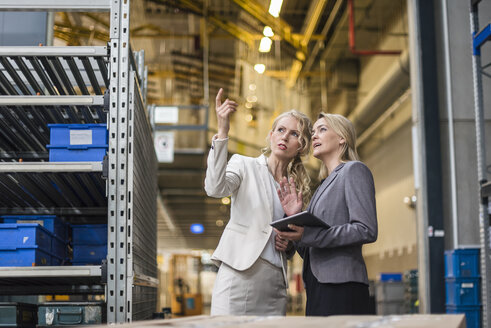 Two women with tablet talking in factory storehouse - DIGF05335