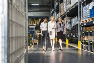 Three women with tablet walking and talking in factory storehouse - DIGF05338