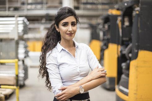 Portrait of confident woman in factory shop floor - DIGF05344