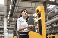 Woman with tablet in factory shop floor looking around - DIGF05347