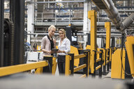 Two women with tablet talking in factory shop floor - DIGF05350