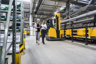 Two women with tablet walking and talking in factory shop floor - DIGF05356