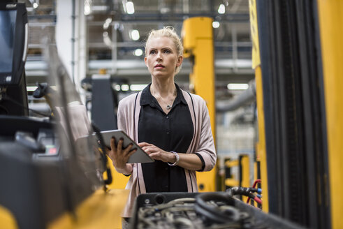 Woman holding tablet in factory shop floor - DIGF05359