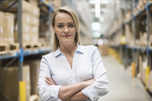 Portrait of confident woman in factory storehouse - DIGF05362