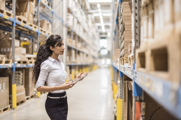 Woman with tablet in factory storehouse looking at shelf - DIGF05365