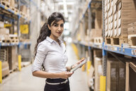 Portrait of confident woman holding tablet in factory storehouse - DIGF05368