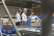 Three women discussing at conveyor belt in factory - DIGF05374