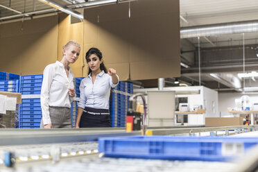 Two women discussing at conveyor belt in factory - DIGF05377