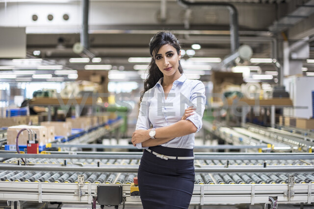 Portrait of confident woman at conveyor belt in factory - DIGF05380 - Daniel Ingold/Westend61