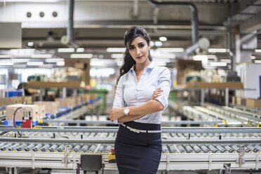 Portrait of confident woman at conveyor belt in factory - DIGF05380