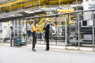 Two women talking in factory shop floor with industrial robot - DIGF05383