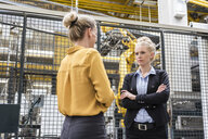 Two women talking in factory shop floor with industrial robot - DIGF05386