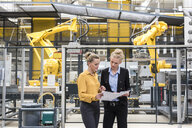 Two women discussing plan in factory shop floor with industrial robot - DIGF05389