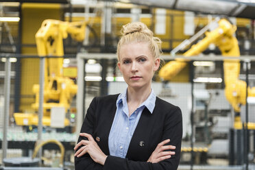 Portrait of confident woman in factory shop floor with industrial robot - DIGF05392