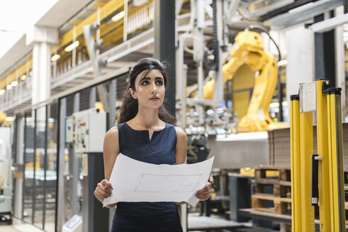 Woman holding plan in factory shop floor with industrial robot - DIGF05395
