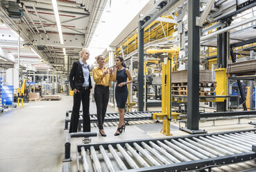 Three women discussing at conveyor belt in factory - DIGF05398