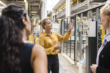 Woman explaining machine to colleagues in modern factory - DIGF05401