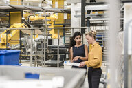 Woman explaing explaining workpiece to businesswoman in factory - DIGF05404