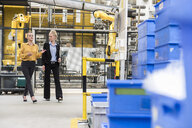 Two women walking and talking in factory shop floor with industrial robot - DIGF05407