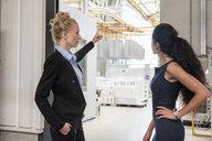 Two women talking in modern factory - DIGF05410