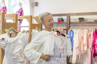 Smiling senior woman shopping for clothes in a boutique - VGF00020