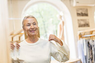Smiling senior woman trying on pullover in a boutique - VGF00026